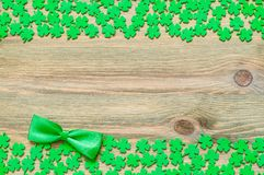St Patricks Day background, double border with green quatrefoils and bow tie. On the wooden background royalty free stock photography
