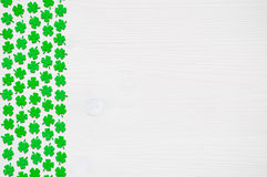 St Patricks Day background with green quatrefoils. St Patricks Day background - border of green quatrefoils on the white wooden surface stock photography