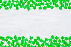 St Patricks Day background with green quatrefoils. St Patricks Day background - borders of green quatrefoils on the white wooden surface Stock Photos