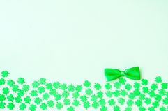 St Patricks Day background - green quatrefoils and bow tie. On the light green wooden background royalty free stock photos