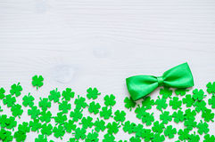St Patricks Day background. St Patricks Day - green quatrefoils and bow tie on the white wooden background royalty free stock photography