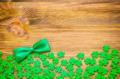 St Patricks Day background. Green quatrefoils and bow tie on the wooden background royalty free stock images