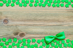 St Patricks Day background. Green quatrefoils and bow tie on the wooden background royalty free stock image