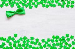 St Patricks Day background with green quatrefoils and green bow tie. St Patricks Day background - bright green quatrefoils and bow tie on the white wooden stock photos