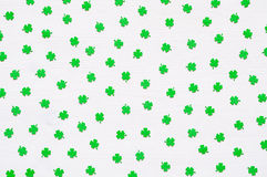 St Patricks Day background with green quatrefoils on the white background. St Patricks Day holiday background - green quatrefoils on the white wooden surface royalty free stock photo