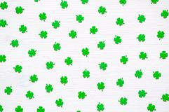 St Patricks Day background with green quatrefoils on the white background. St Patricks Day holiday background, green quatrefoils on the white wooden surface royalty free stock image