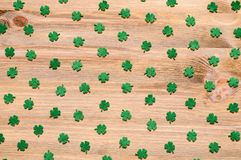 St Patricks Day background with green quatrefoils on the wooden background. St Patricks Day background - green quatrefoils on the natural wooden surface royalty free stock images