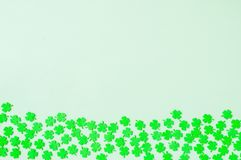 St Patricks Day background with green quatrefoils on the wooden background. St Patricks Day background - border of green quatrefoils on the light green wooden stock images