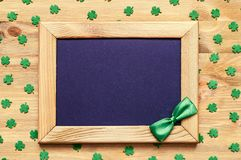 St Patricks Day background with green quatrefoils on the wooden background. St Patricks Day background - wooden frame with green bow tie and free space for text stock photo