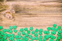 St Patricks Day background. With green quatrefoils on the wooden surface royalty free stock photos