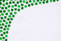 St Patricks Day background - one side curved border of green quatrefoils on the white wooden surface. St Patricks Day background - one side border of green royalty free stock image
