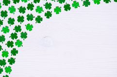 St Patricks Day background - one side curved border of green quatrefoils on the white wooden surface. Free space stock images
