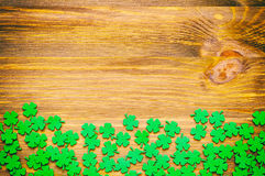 St Patricks Day background. St Patrick`s Day background with green quatrefoils on the wooden background royalty free stock photography