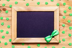 St Patricks Day background with quatrefoils and wooden frame with bowtie on the wooden background. St Patricks Day background. Wooden frame with green bow tie stock image