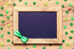 St Patricks Day background with green quatrefoils and wooden frame with bowtie on the wooden background. St Patricks Day background. Wooden frame with green bow Royalty Free Stock Photography
