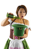 St Patricks Day Bartender. Young Asian female bartender dressed in costume for St Patrick's Day performing a magic trick Stock Photos
