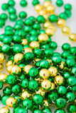 St. patricks day beads in gold and green colors. St. patricks day, beads in gold and green colors, close up and isolated on white background, vertical Stock Image