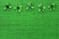 St Patricks Day border of paper shamrocks on green burlap Royalty Free Stock Photos