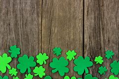 St Patricks Day bottom border of shamrocks over rustic wood. St Patricks Day bottom border of shamrocks over a rustic wooden background Stock Photo