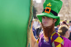 St. Patricks Day in Bucharest, Romania. Unidentified young man wearing traditional Irish green hat holds large green flag during the 2nd St. Patricks Day Parade Stock Images