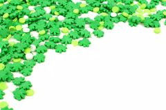 St Patricks Day candy border. St Patricks Day corner border of green shamrock candy sprinkles over white Royalty Free Stock Image