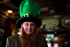 St Patricks Day Celebration. A old man smiling and laughing as he is wearing the hat and wig to celebrate St Pactrick's Day Stock Photos