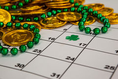 St. Patricks Day chocolate gold coins and beads kept on calendar Stock Photography