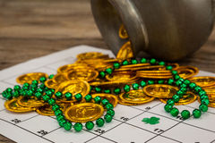 St. Patricks Day chocolate gold coins and beads kept on calendar Royalty Free Stock Images