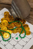 St. Patricks Day chocolate gold coins and beads kept on calendar Stock Photos