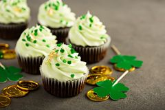 St Patricks day chocolate mint cupcakes. With green sprinkles and golden leaf Stock Photography