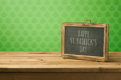 St. Patricks day concept with chalkboard on wooden table. Over wallpaper background Royalty Free Stock Photography