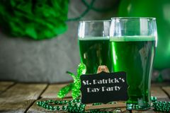 St. Patricks day concept - green beer and symbols. Rustic background. Part invitation Stock Photography