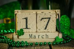 St. Patricks day concept - green beer and symbols. Wood calendar, rustic background Stock Photo
