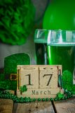 St. Patricks day concept - green beer and symbols. Wood calendar, rustic background Stock Photography