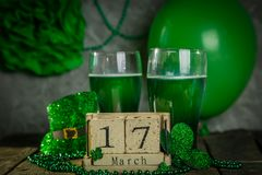St. Patricks day concept - green beer and symbols. Wood calendar, rustic background Royalty Free Stock Photos
