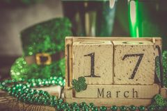 St. Patricks day concept - green beer and symbols. Wood calendar, rustic background Stock Images
