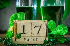 St. Patricks day concept - green beer and symbols. Wood calendar, rustic background Royalty Free Stock Photography