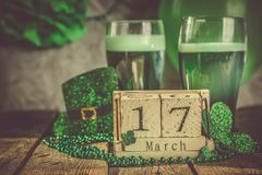 St. Patricks day concept - green beer and symbols. Wood calendar, rustic background Royalty Free Stock Image