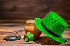 St Patricks day concept with pot full gold coins, horseshoe, gre. En hat and shamrock on vintage wooden background, close up Stock Photo