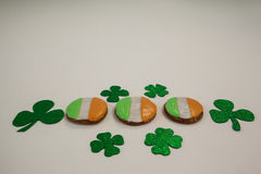 St. Patricks Day cookies decorated with irish flag surrounded with shamrocks. On white background Royalty Free Stock Photo