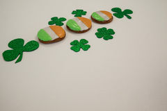 St. Patricks Day cookies decorated with irish flag surrounded with shamrocks. On white background Royalty Free Stock Images