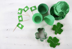 St Patricks Day cooking and baking concept. Happy St Patricks Day cooking and baking concept with green cupcake pans and shamrock cookie cutter  on vintage style Stock Image