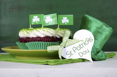St Patricks Day cupcakes with greeting tag. Happy St Patricks Day cupcakes with green theme decorations on vintage style green wood background Royalty Free Stock Photos