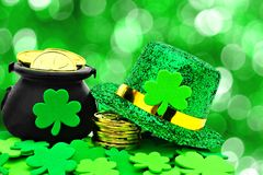 St Patricks Day decor. St Patricks Day Pot of Gold, hat and shamrocks over a green background Stock Photo