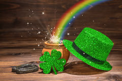 St Patricks day decoration with magic light rainbow pot full gol. D coins, horseshoe, green hat and shamrock on vintage wooden background, close up Stock Photo