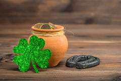 St Patricks day decoration with pot of gold coins, horseshoe and. Light shamrock on vintage wooden background, close up Royalty Free Stock Image