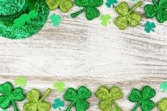 St Patricks Day double border of shamrocks, leprechaun hat over white wood. St Patricks Day double border of shamrocks with leprechaun hat over a rustic white stock photos