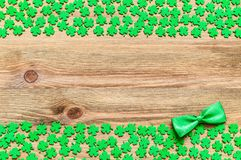 St Patricks Day festive background. St Patricks Day background. Green quatrefoils and bow tie on the wooden background, free space for text royalty free stock photos
