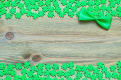St Patricks Day festive background. Green quatrefoils and bow tie on the wooden background royalty free stock photo