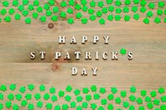 St Patricks Day festive background. Green quatrefoils on the wooden background and inscription Happy St Patrick`s day. St Patrick`s Day background. Green royalty free stock images